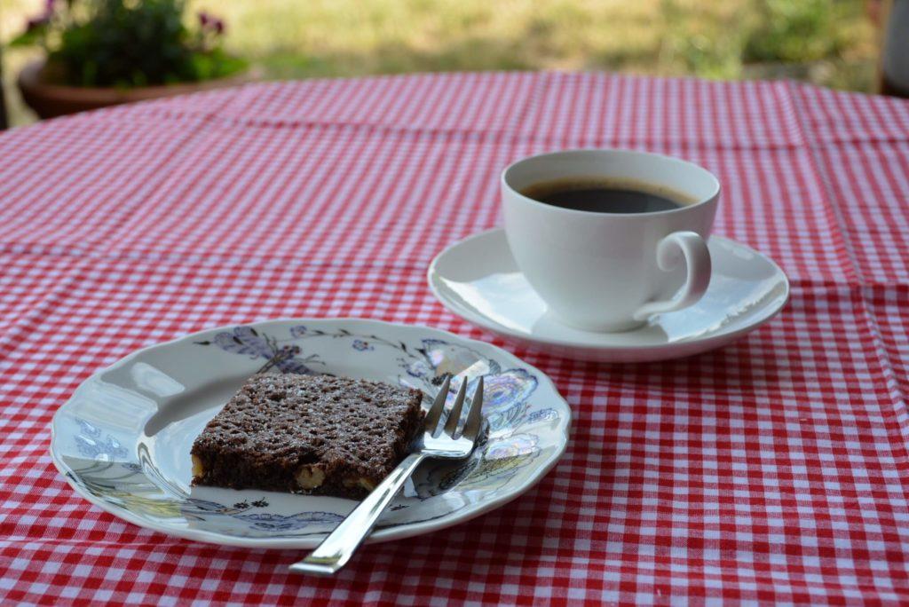 Kawałek ciasta czekoladowego na talerzyku z widelczykiem, obok kawa w białej filiżance, stół nakryty serwetą w biało-czerwoną kratkę - Najlepsze brownie na świecie