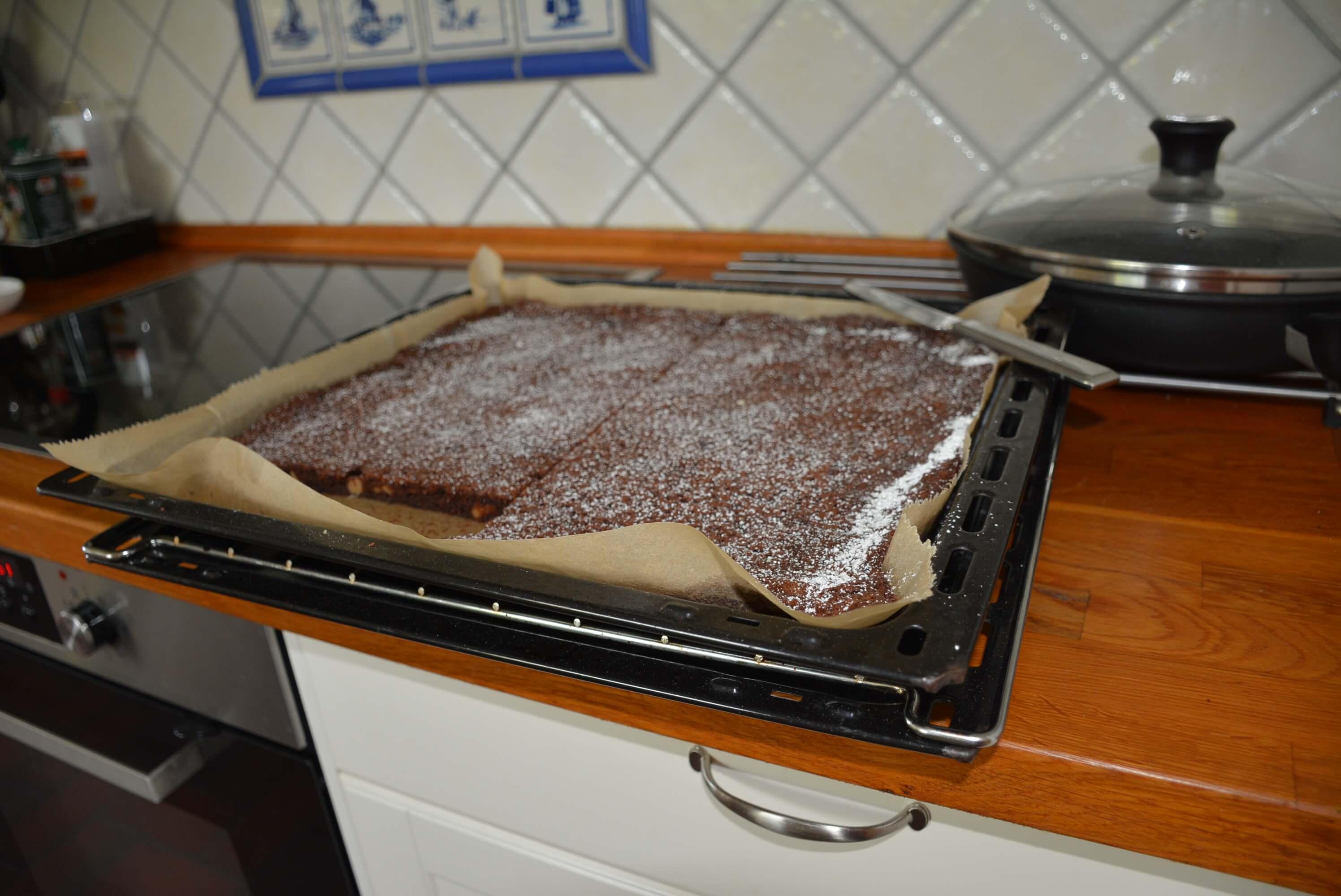 Ciasto czekoladowe wyciągnięte z piekarnika, blacha leży na drewnianym blacie kuchennym - Najlepsze brownie na świecie