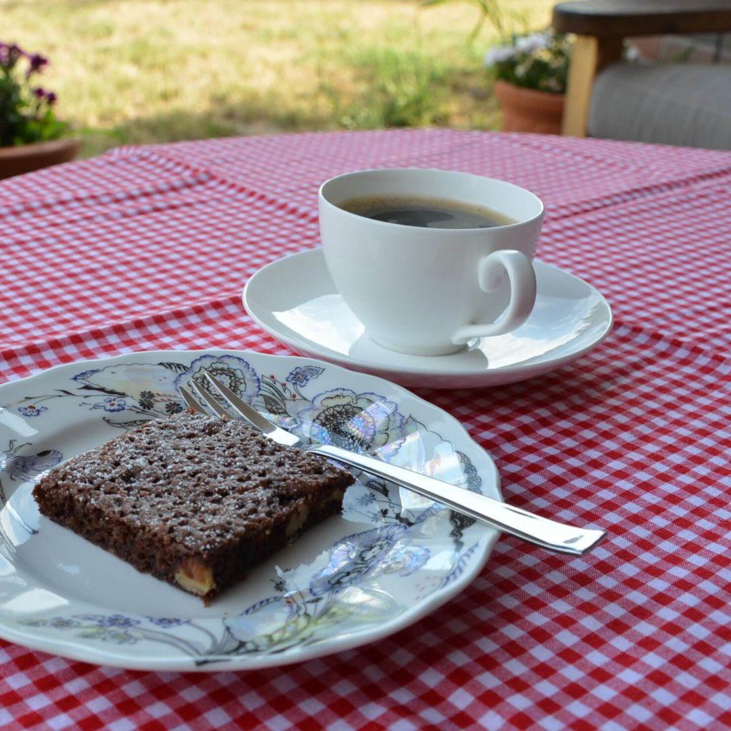 Ciasto czekoladowe i kawa w białej filiżance na obrusie w biało-czerwoną kratkę - Najlepsze brownie na świecie
