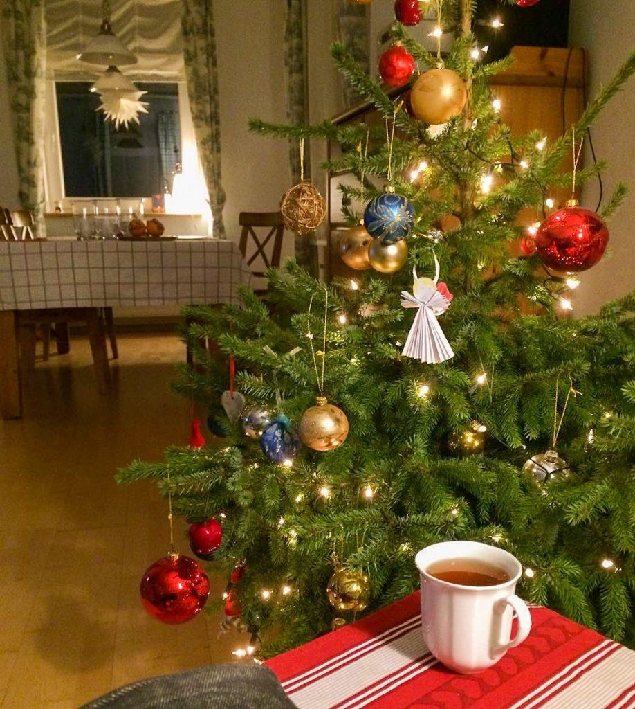 Udekorowana zielona choinka, w tle gwiazda w oknie, z przodu kubek z herbatą na czerwonej serwetce - Grudniowe przyjemnostki