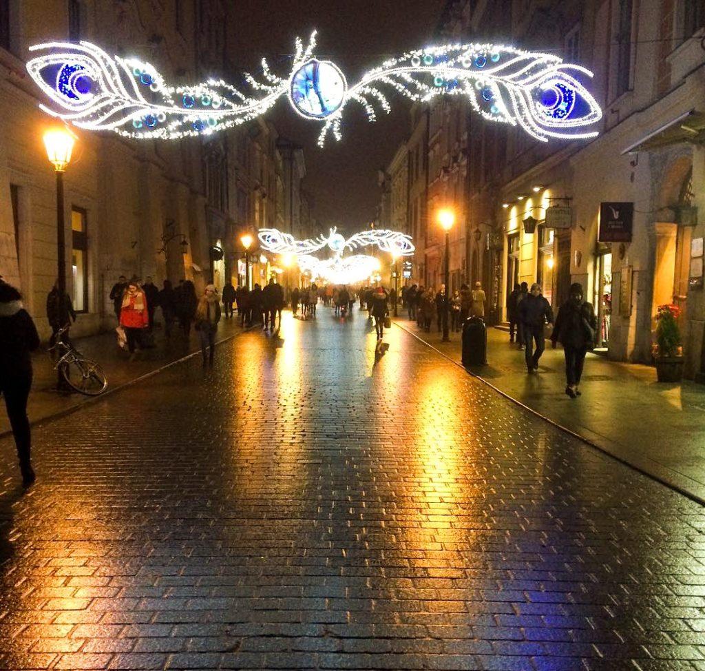 Ulica Floriańska w Krakowie, ludzie, dekoracyjne światełka świąteczne odbijające się na mokrym bruku - Grudniowe przyjemnostki