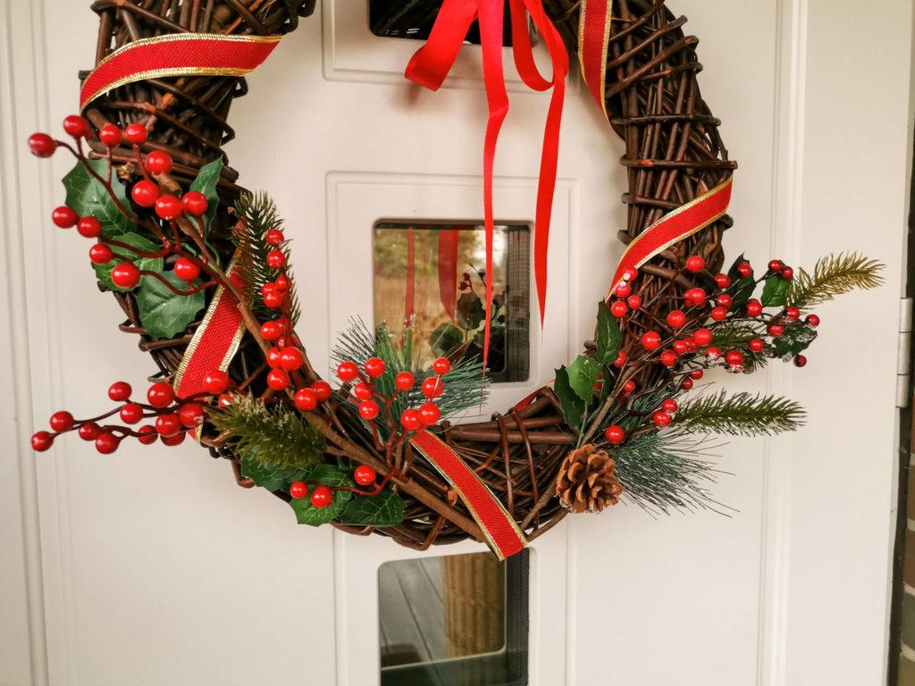Świąteczny wiklinowy wieniec na drzwi z czerwoną wstążką i gałązkami - Grudniowe przyjemnostki