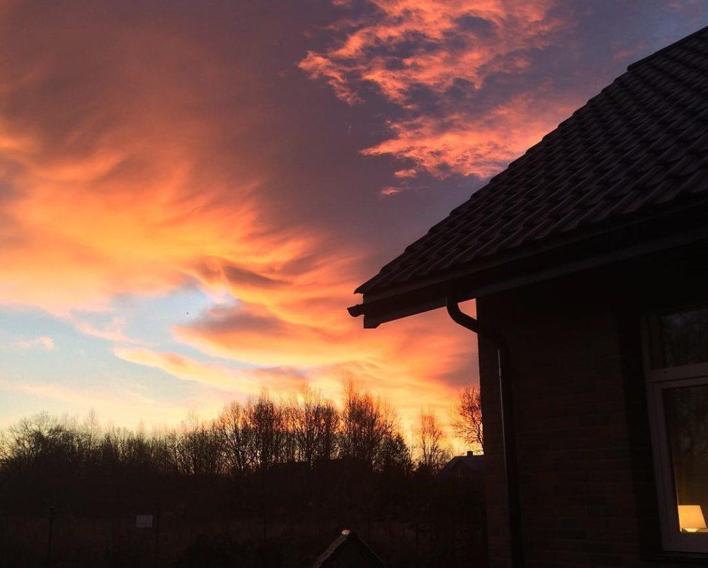 Wschód słońca zimą, niebo w kolorze różowo-pomarańczowo-nieboieskim, zarysowany kontur domu